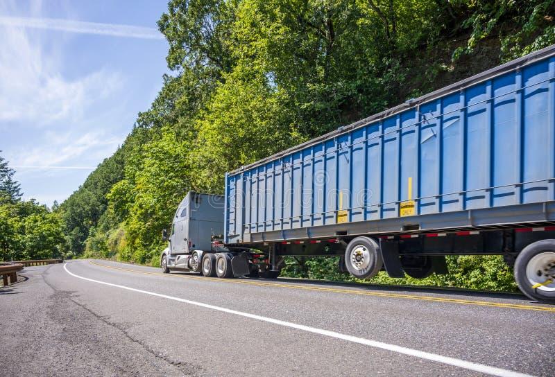 Industrieller halb LKW der großen Anlage mit langer Masse bedeckte halb den Anhänger, der auf kurvenreiche Straße mit grünem Wald lizenzfreie stockfotos