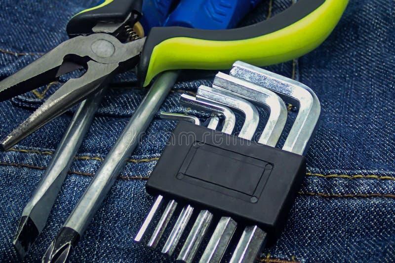 Industrieller Hintergrundhandwerkzeugmöbelreparaturschraubenzieher-Zangenschlüssel auf dunkler Textiloberfläche stockfotos
