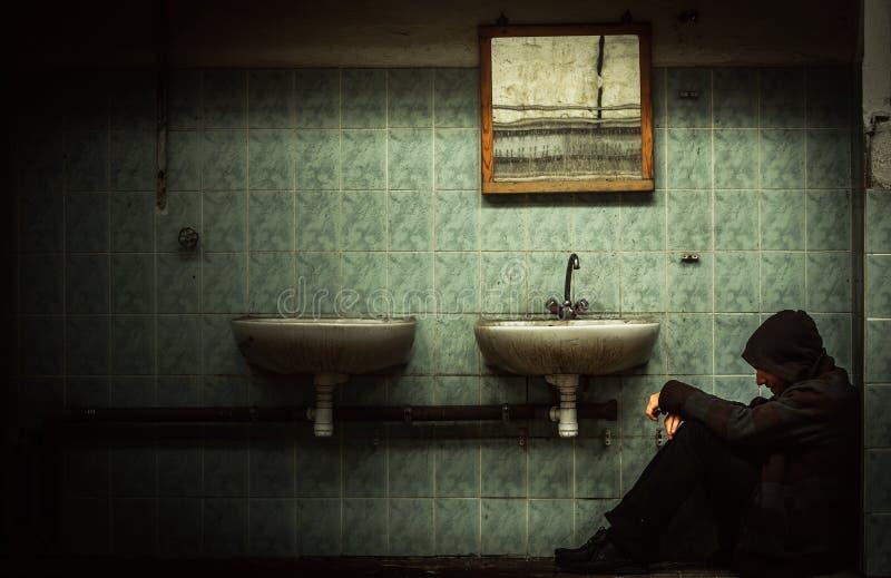 Industrieller Innenraum mit einem deprimierten Mann lizenzfreie stockbilder