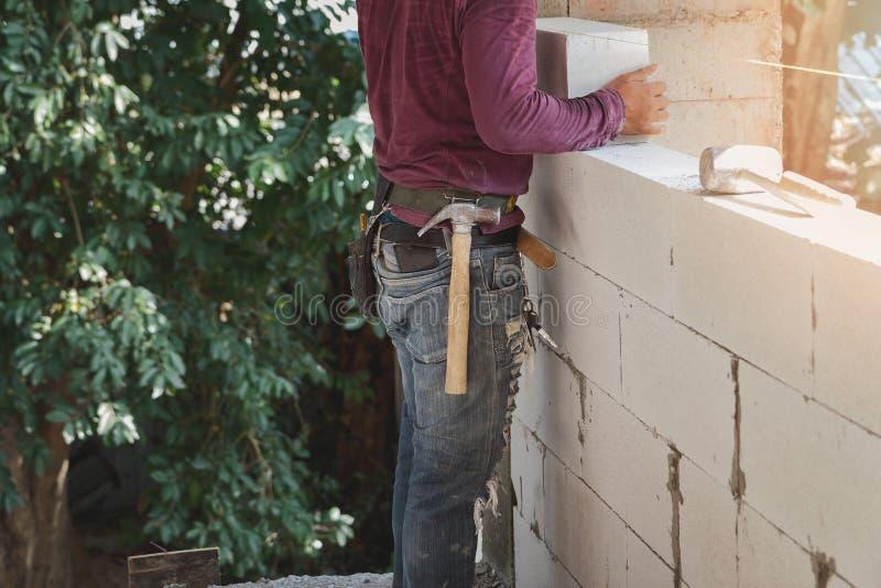 Industrieller Maurer, der Ziegelsteine auf Baustelle installiert stockbilder
