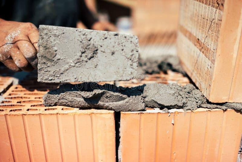 Industrieller Maurer, der Ziegelsteine auf Baustelle installiert lizenzfreie stockfotografie