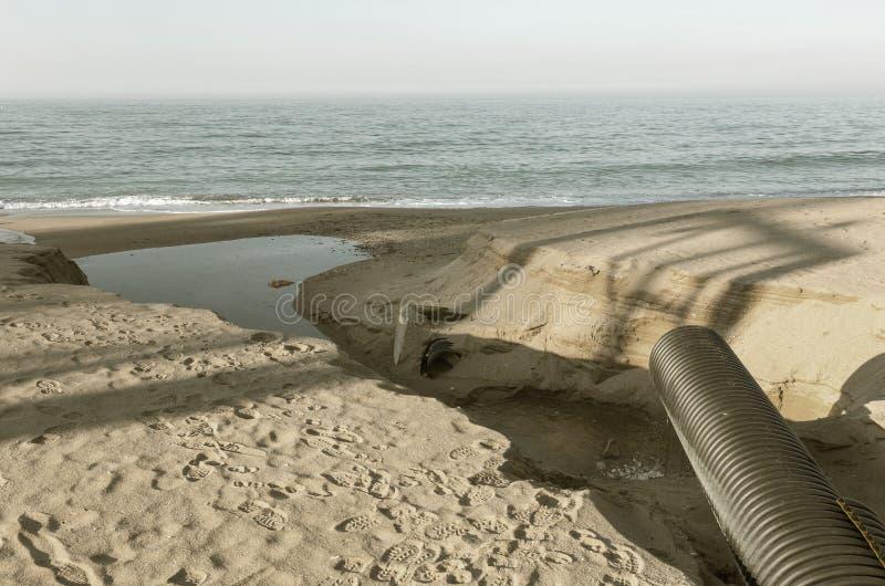Industrielles Abwasser, die Rohrleitung entlädt flüssige Industrieabfälle in das Meer auf einem Stadtstrand Schmutzige Abwasserfl stockfotos
