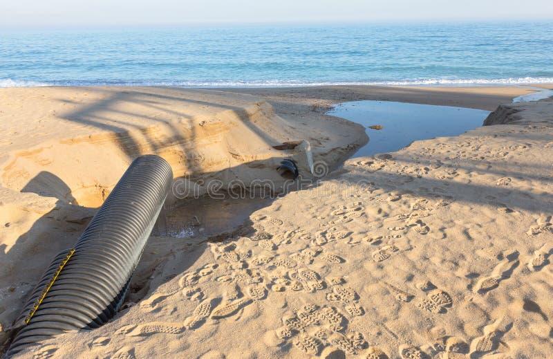 Industrielles Abwasser, die Rohrleitung entlädt flüssige Industrieabfälle in das Meer auf einem Stadtstrand Schmutzige Abwasserfl stockfoto