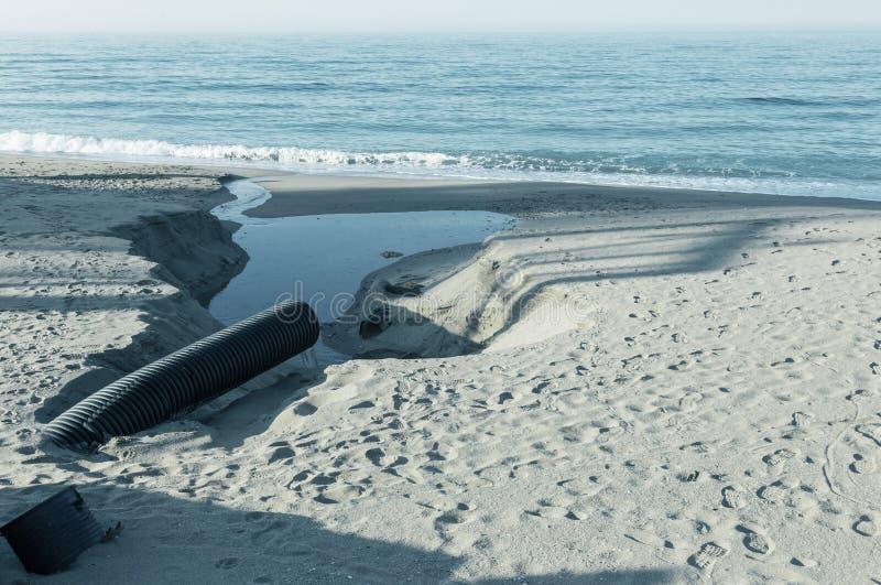 Industrielles Abwasser, die Rohrleitung entlädt flüssige Industrieabfälle in das Meer auf einem Stadtstrand Schmutzige Abwasserfl lizenzfreie stockfotos