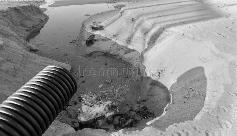 Industrielles Abwasser, die Rohrleitung entlädt flüssige Industrieabfälle in das Meer auf einem Stadtstrand Schmutzige Abwasserfl lizenzfreies stockbild