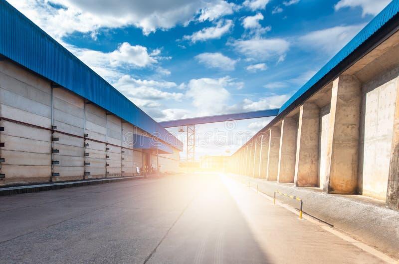 Industrielles Lager Straße zwischen blauen Lagern mit dem Sonnenuntergang Unterschiedliche Kugel 3d stockfotografie
