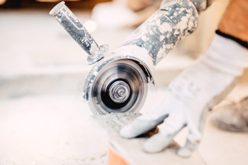 Industrielles Werkzeug, Schleifer, der Stück des Steins schneidet Marmorausschnitt an der Baustelle lizenzfreie stockbilder