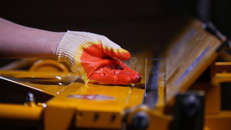industriellt begrepp En arbetare som böjer detaljerna med en tryckmaskin royaltyfri fotografi