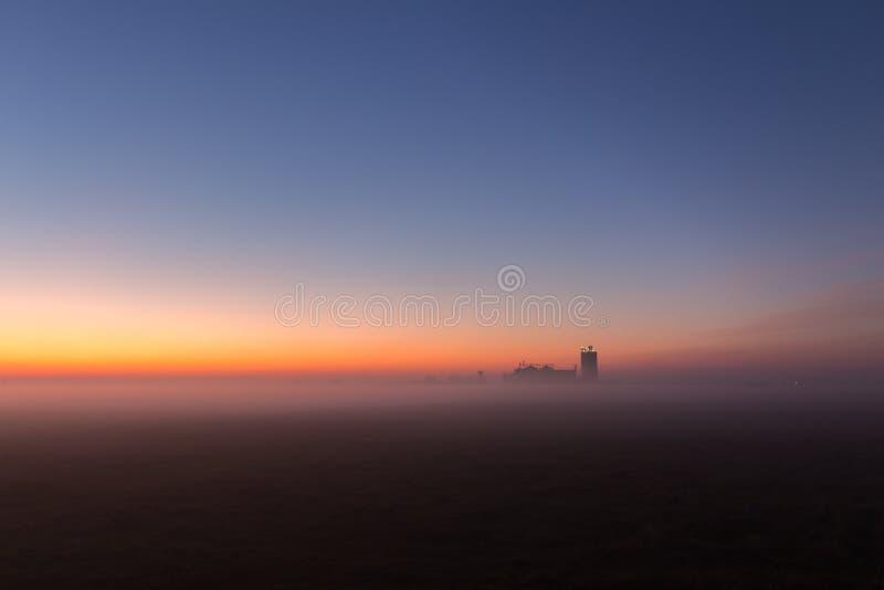 Industriellt dimmigt landskap, kontur av den gamla fabriken mot solnedgånghimlen och misten på den blåa timmen på natten royaltyfria foton