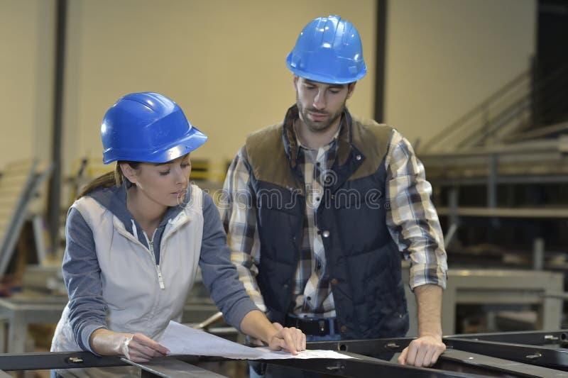 Industriellt folk som möter i fabrik royaltyfri foto