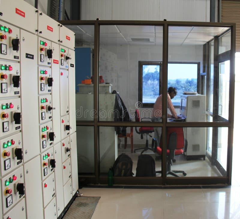 Industriellt kontrollera rum med operatören och kontrollera stiger ombord arkivbild