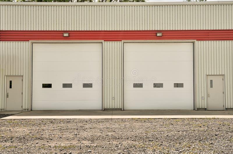 Industriellt lager med vita rulldörrar arkivbilder