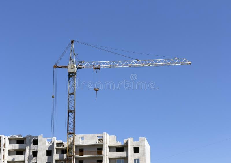Industriellt landskap, byggande kran mot den blåa himlen arkivbild