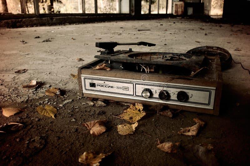 Industriellt landskap - gammal bruten skivtallrik bland de gulnade sidorna på golvet av övergiven byggnad royaltyfri fotografi