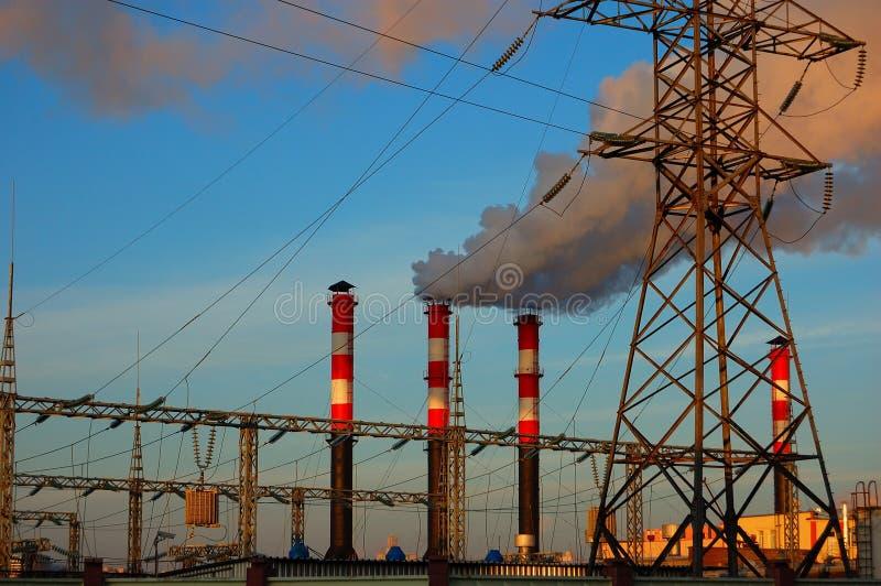 Industriellt landskap och rör med en rök mot bakgrunden av himlen royaltyfri foto