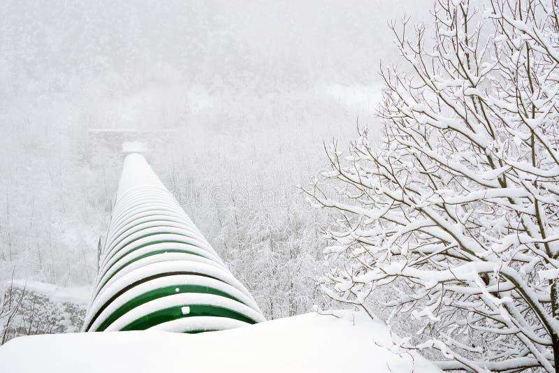 Industriellt rör över en alpin dal i vinter royaltyfria foton