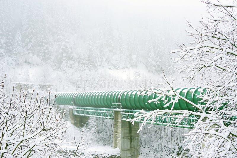 Industriellt rör över en alpin dal i vinter royaltyfri bild