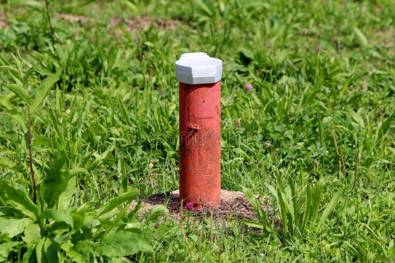 Industriellt rött delvist rostat rör som täckas med locket för vit metall på hård betonggrund som omges med oklippt grönt gräs fotografering för bildbyråer