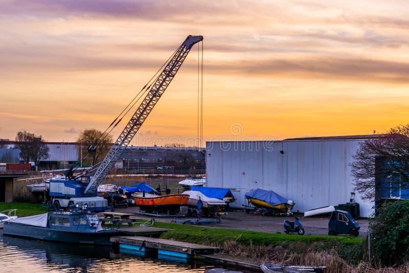 Industriezone met water en boten bij zonsondergang, de haven van het hol Rijn, Nederland van Alphen aan royalty-vrije stock fotografie