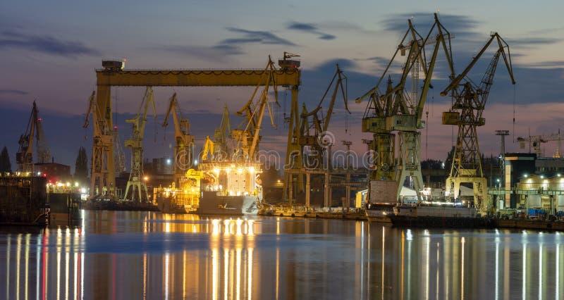 Industriområden, skeppsvarv och port efter solnedgången - Szczecin, Pol fotografering för bildbyråer