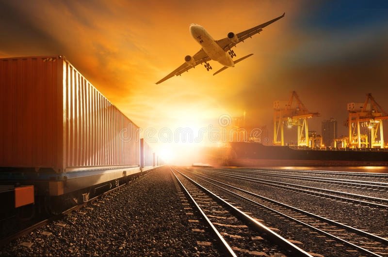 Industry container trainst running on railways track and commercial ship in port ,plane air cargo flying above use for land. Air ,and vessel transport industry royalty free stock photos