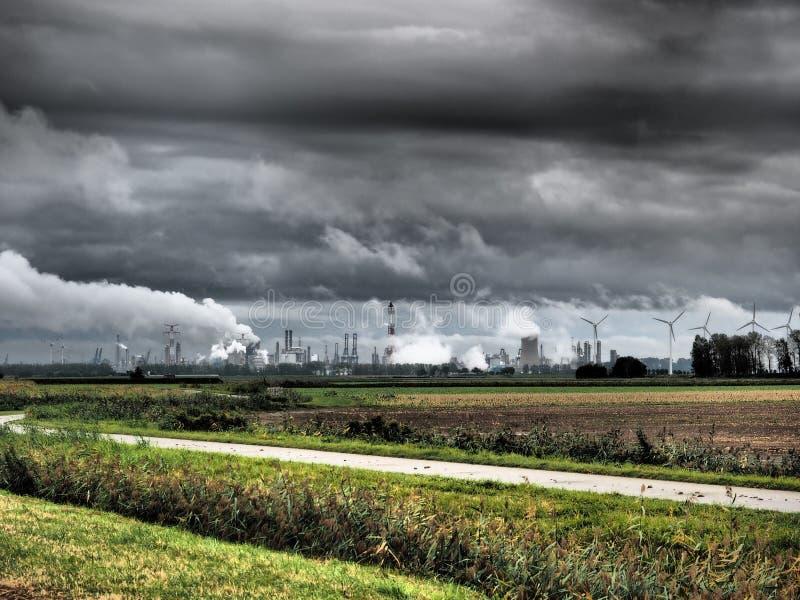 Industry, smoke stacks and wind turbines behind a green field under dark clouds near Antwerp stock photo