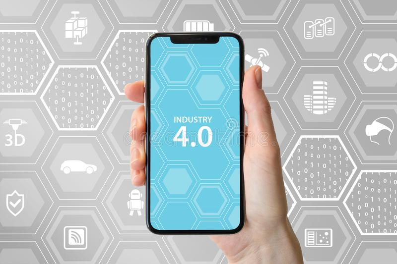 Industry 4.0 text displayed on smartphone screen. Hand holding modern frameless smart phone in front of neutral background.  royalty free stock image
