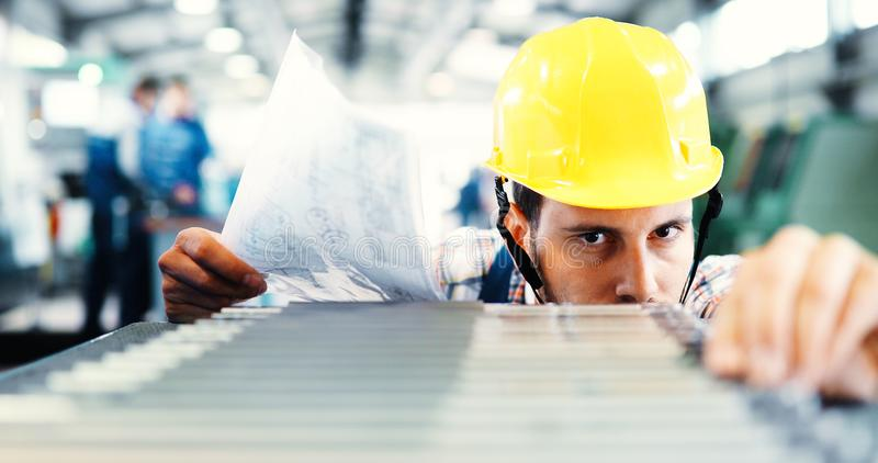 Industry Worker entering data in CNC machine at factory. Industry Worker working on cnc machine in metal industry factory royalty free stock photos