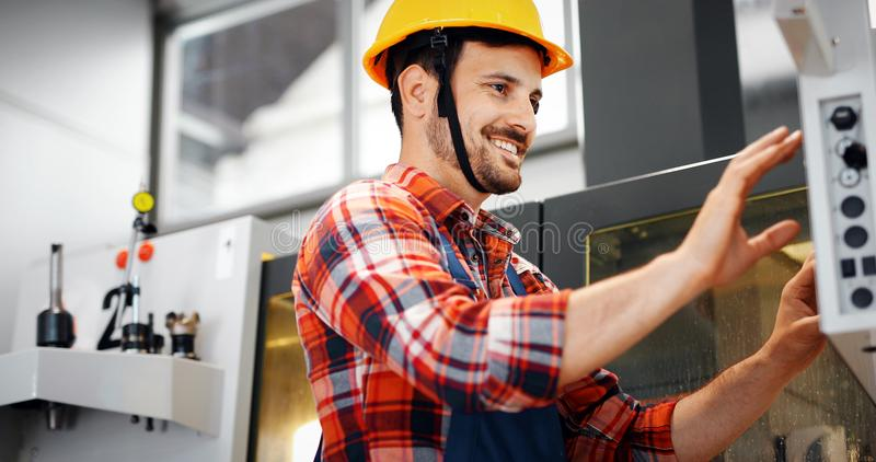 Industry Worker entering data in CNC machine at factory. Industry Worker working on cnc machine in metal industry factory royalty free stock photo