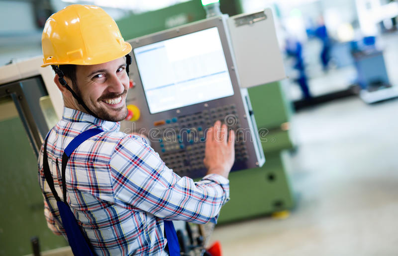 Industry Worker entering data in CNC machine at factory. Industry Worker working on cnc machine in metal industry factory stock photography