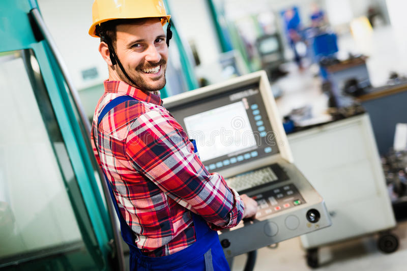 Industry Worker entering data in CNC machine at factory. Industry Worker working on cnc machine in metal industry factory stock image