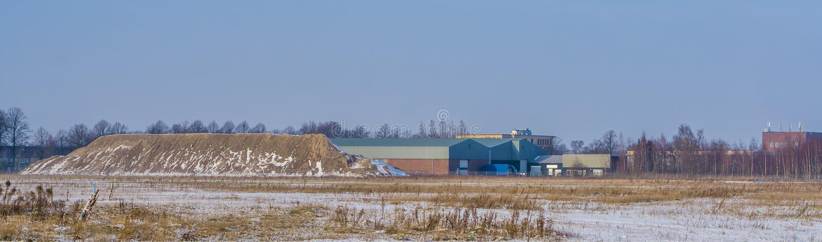 Industry zone with a sand mountain and a warehouse, Majoppeveld a dutch industrial terrain in the city of Roosendaal, The. A Industry zone with a sand mountain royalty free stock image