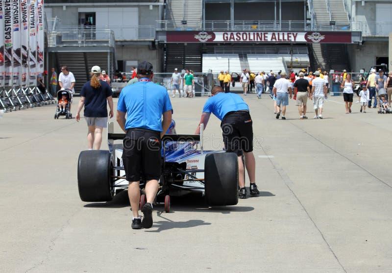 Indy 500 miembros del equipo de la raza que empujan un coche de carreras al callejón de la gasolina fotos de archivo