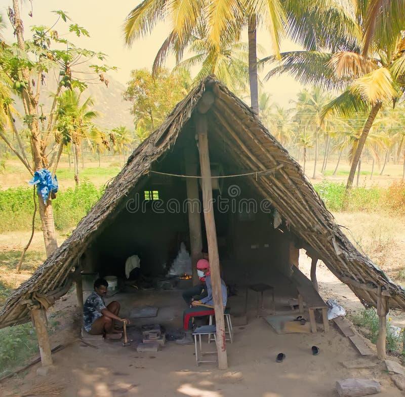 indyjski życie Pierwotny wioski smithy w drzewko palmowe gaju i blacksmiths z narzędziami zdjęcie stock