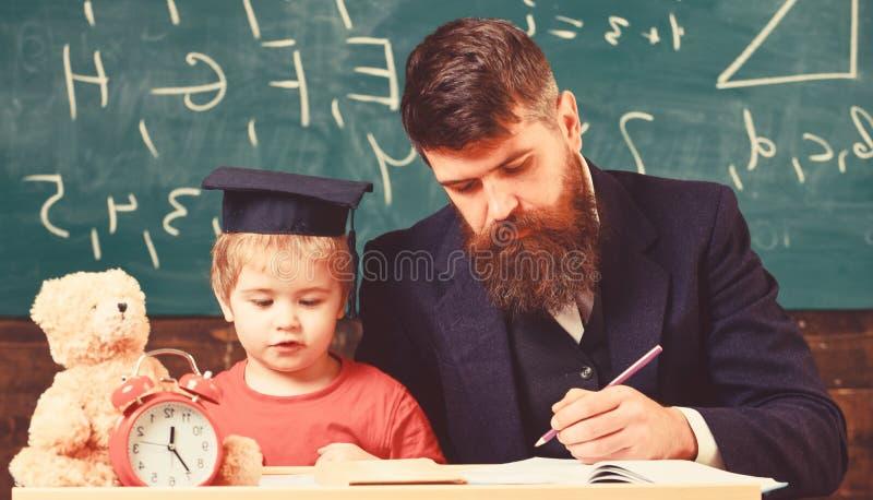 Indywidualna lekcja z pierwszy r?wniark? Nauczyciel i ucze? w mortarboard w sala lekcyjnej, chalkboard na tle jednostka zdjęcie stock