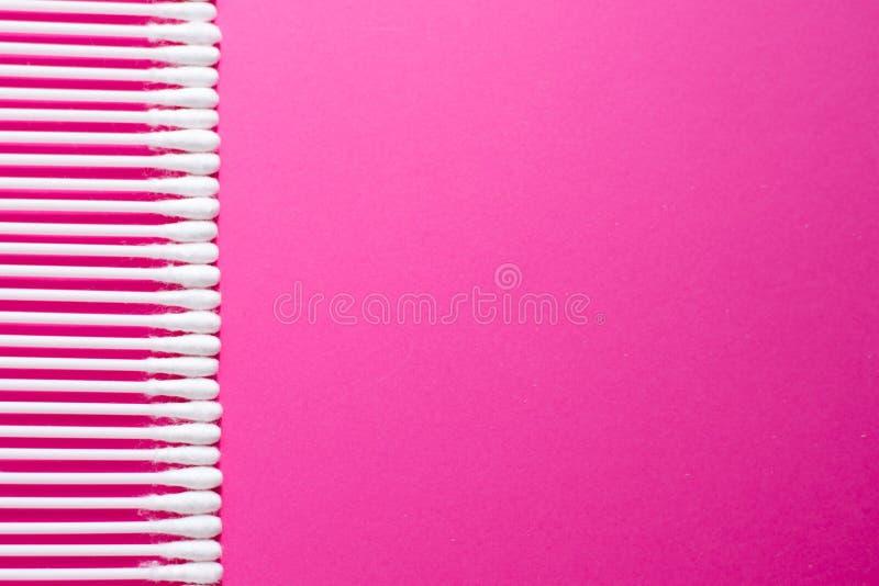 Indywidualni uszaci kije z plastikowymi wyboru i bawełny pączkami z selekcyjną ostrością na różowym tle Czyści uszatych mopy dla  obrazy stock