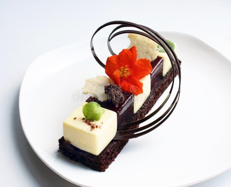 Indywidualny deser z jadalną kwiatu i czekolady dekoracją na bielu talerzu obraz royalty free