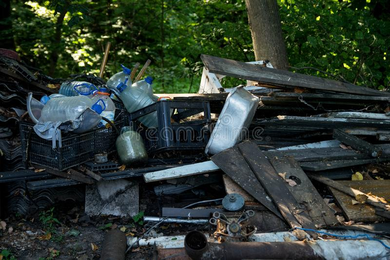Inefficient waste from metal pipes, wooden boards, plastic bottles. Dumped in the forest royalty free stock photography