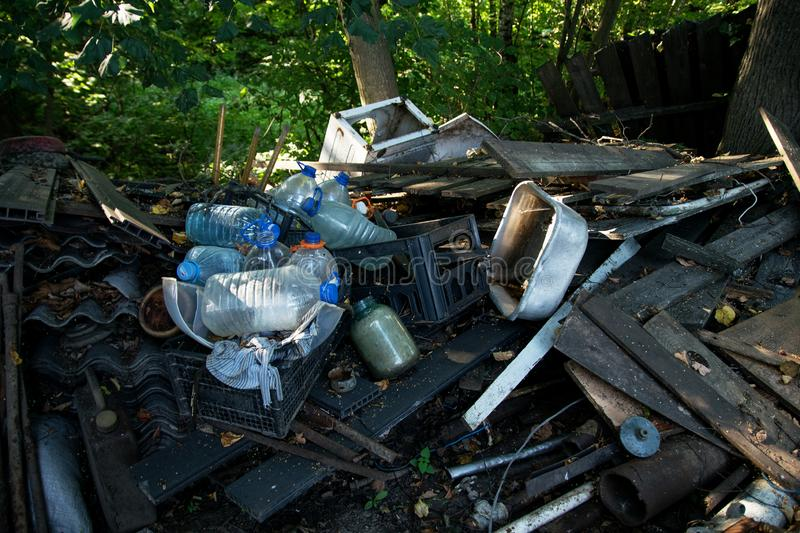 Inefficient waste from metal pipes, wooden boards, plastic bottles and slate. Dumped in the forest in the trash stock photos