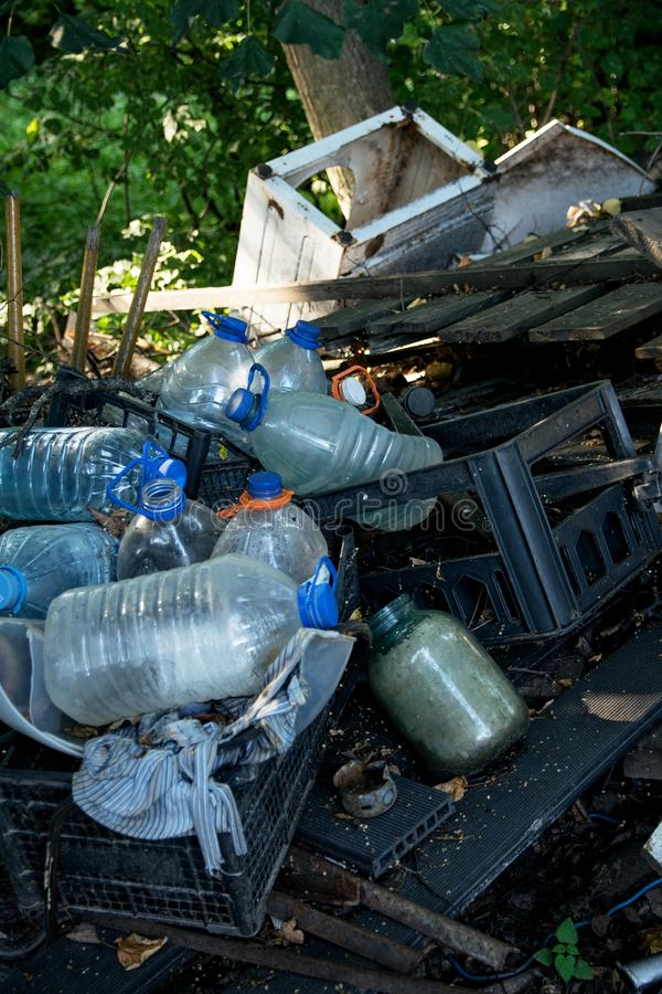 Inefficient waste from wooden boards and plastic bottles. Dumped in the forest in the trash royalty free stock images