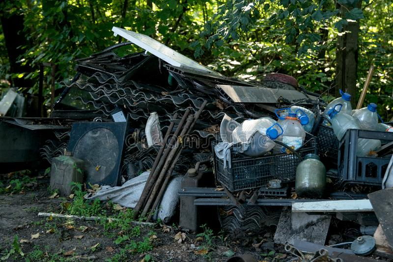 Inefficient waste from wooden boards, plastic bottles and slate dumped. In the forest in the trash stock image