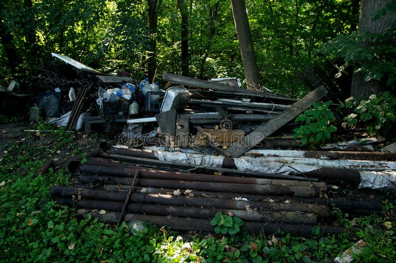 Inefficient waste from wooden boards, plastic bottles and slate dumped. Inefficient waste from metal pipes, wooden boards, plastic bottles dumped in the forest stock photo