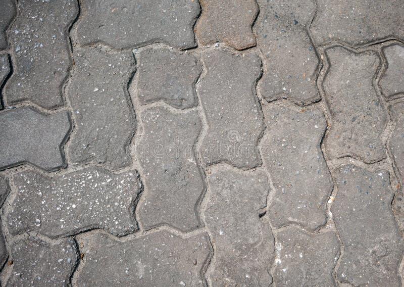 Ineinander greifenpflasterung mit den grauen und weißen Betonblöcken stockfotografie