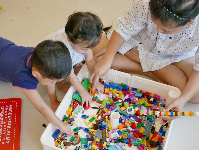 Ineinandergreifende Plastikziegelsteine in Mutter ` s Händen, die mithilfe von ihren zwei kleinen Babys errichtet werden lizenzfreie stockfotos