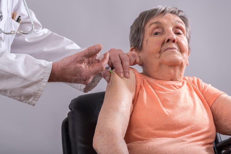 Inenting van een oude vrouw stock foto's