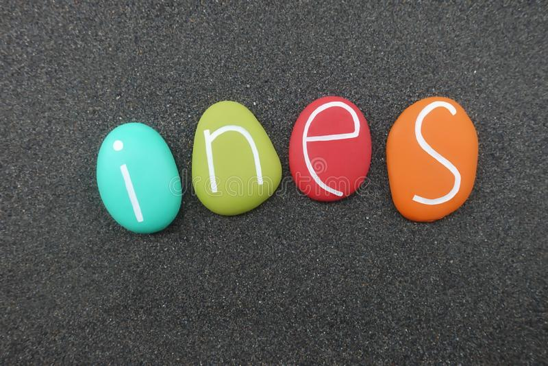 Ines, nom donné féminin avec les pierres colorées au-dessus du sable volcanique noir photographie stock libre de droits