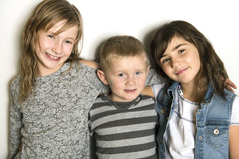 Infância, amor, felicidade e ligações de família Retrato interno de irmãs e do irmão bonitos bonitos das crianças imagem de stock royalty free