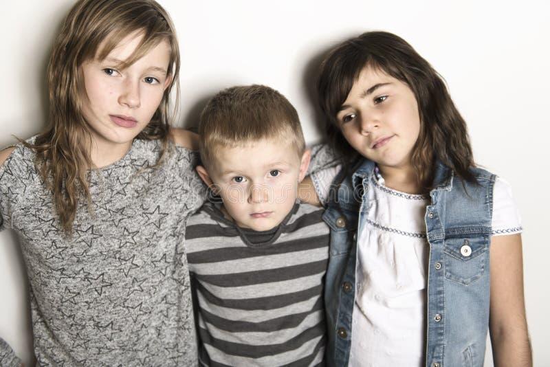 Infância, amor, felicidade e ligações de família Retrato interno de irmãs e do irmão bonitos bonitos das crianças fotografia de stock