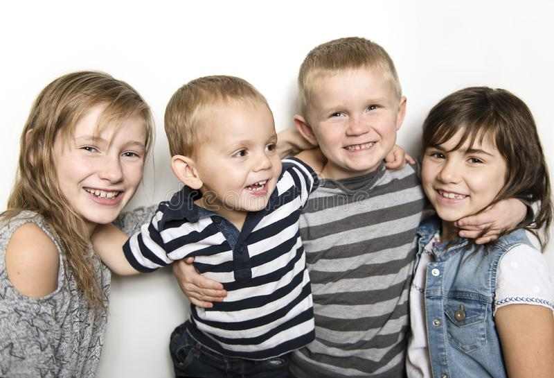 Infância, amor, felicidade e ligações de família Retrato interno de irmãs e do irmão bonitos bonitos das crianças imagem de stock