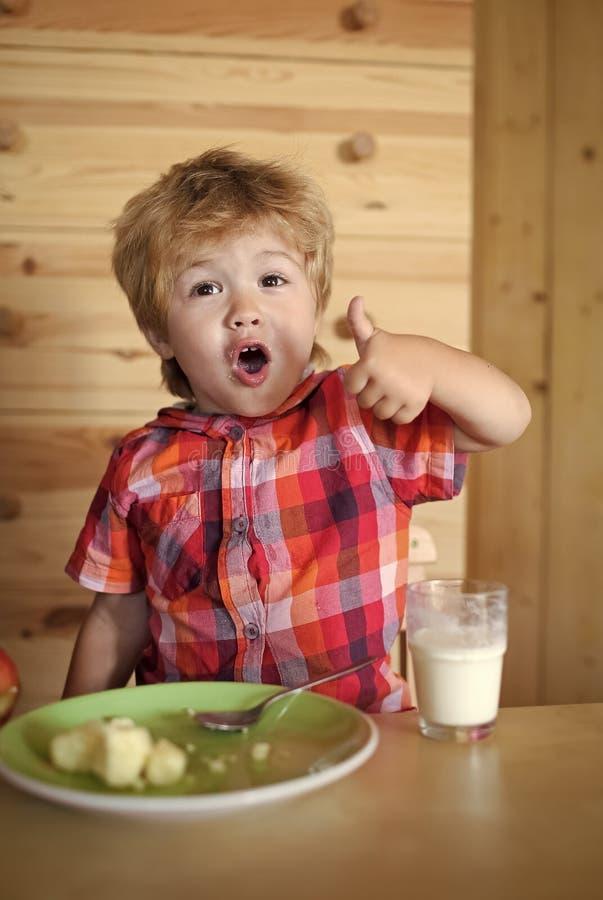 Infância Criança ou menino feliz louro que comem na tabela foto de stock royalty free